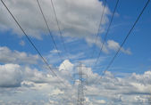 Power lines on the blue sky with cloudy background — Stock Photo