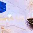 A close up image of a white decorative Christmas ornamental orb on a white fir tree branch with the blue lighting. — Stock Photo