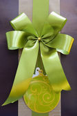 Brown gift box with green ribbon bow — Stock Photo