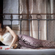 Gorgeous asian woman in thai dress lying on bed — Stock Photo #28695971