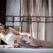 Gorgeous asian woman in thai dress lying on bed — Stock Photo #28696037