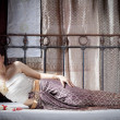 Gorgeous asian woman in thai dress lying on bed — Stock Photo