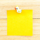 Yellow blank paper with the clip on the wooden background — Stock Photo