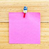 Rosa carta bianca con la clip sullo sfondo in legno — Foto Stock