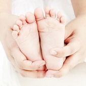 Mother hold baby leg together in your hand — Stock Photo