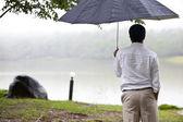 Male back under umbrella in the park — Stock Photo