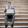 Handsome businessman having phone call and using laptop — Stockfoto