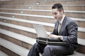 Handsome businessman using laptop — Stock Photo