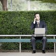 Businessman talking on phone and using laptop — Stock Photo