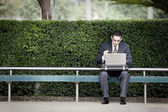 Businessman working laptop and waiting for the bus — Stock Photo
