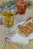 Glasses with different herbal teas and cookies — Stock Photo