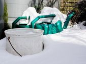 Watering cans in snow — Stock Photo