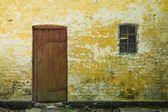 Yellow wall with door and window — Stock Photo