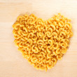 Macaroni forming a heart over a wooden cut board — Stock Photo