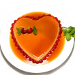 Heart shape flan caramel with strawberries on the edge on white — Stock Photo