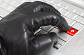 Online delete concept with hand wearing black leather glove pres — Stock Photo