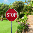 Stop sign against Natural stone landscaping in home garden with — Foto de Stock
