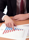 Man in suit and financial papers — Stock Photo