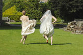 Two women in bridal dresses running on a lawn — Stock Photo