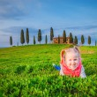 Little girl smiling and playing on a meadow in front of a Tuscan — Stock Photo #44203051