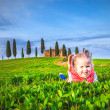 Little girl smiling and playing on a meadow in front of a Tuscan — Stock Photo