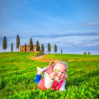 Little girl smiling and playing on a meadow in front of a Tuscan — Stock Photo #44203213