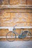 Alleging bike against a wall Tuscan monument — Stock Photo
