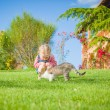 Little girl plays with a cat on a green blade of grass — Stock Photo #47781407