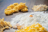 Pasta egg in flour and a rolling pin. — Stock Photo