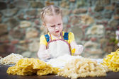 The girl smashing an egg into the flour for pasta. — Stock Photo