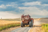 Tractor with a trailer on the fields in Tuscany, Italy — Stock Photo