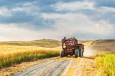 Tractor with a trailer on the fields in Tuscany, Italy — Stock fotografie