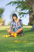 Beautiful woman on the green grass eaten fruits — Stock Photo