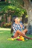 Hermosa mujer sobre la verde hierba come frutas — Foto de Stock