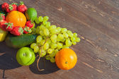 Colorful fruits on brown wood in natural light — Photo