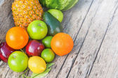 Colorful fruits on brown wood in natural light — Stock Photo