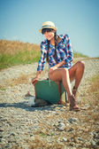 Beautiful brazilian woman with a suitcase on a road trip. — Stock Photo