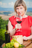 Beautiful woman in a red dress tasting red wine in the hills of — Stock Photo