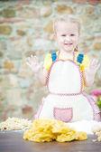Girl preparing pasta dough on wooden table. — Stock Photo