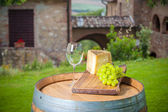 Cheese and grapes on a barrel in the Tuscan landscape Italy — Stock Photo