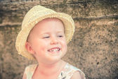 Laughing gorgeous and beautiful little girl in a straw hat — Stock Photo