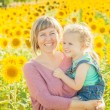 Mother and daughter among sunflowers having fun — Stock Photo #51322979