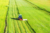 Tractor mowing green field — Stock Photo