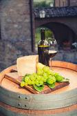 Red wine, pecorino cheese, grapes, bottle and glass on wooden ba — Stockfoto