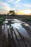 Tire tracks adventure and the puddles at sunset — Stock Photo