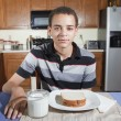 Mixed Race teenager sitting in kitchen with a peanut butter and jelly sandwich and glass of  milk — Stock Photo
