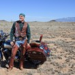 Rugged retired man with his motor cycle in the southwest. — Stock Photo #27677681