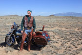 Rugged retired man with his motor cycle in the southwest. — Foto de Stock