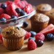 Fruit filled fresh muffins served with variety of organic early spring berries — Stock Photo