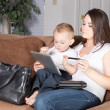 Stock Photo: Young mother and her son enjoying convenience of online shopping from home.